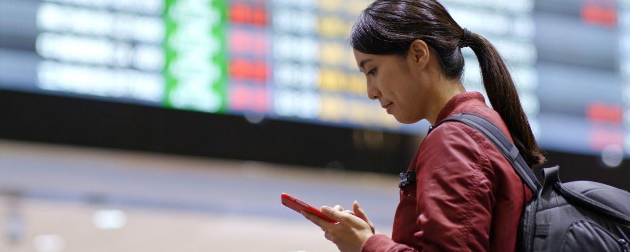 destino turistico inteligente_pasajera mirando el móvil en el aeropuerto
